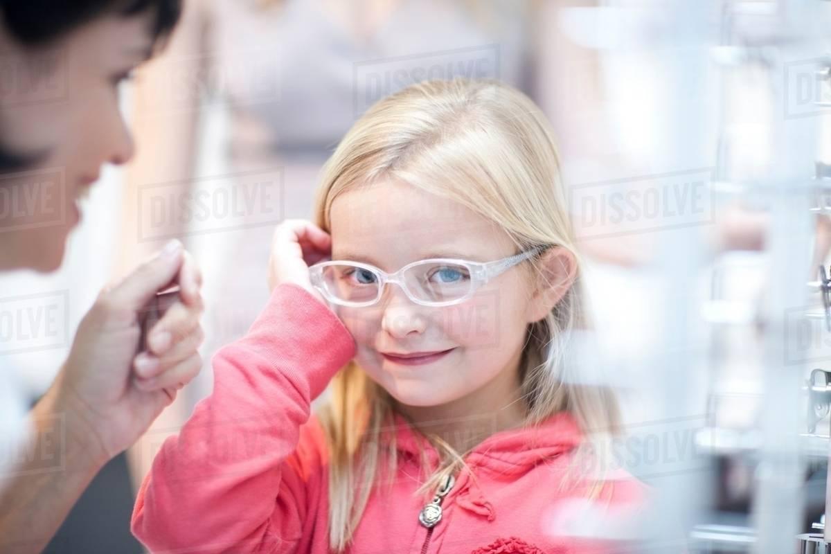 3ee717df51 Young girl on choosing eyeglasses - Stock Photo - Dissolve