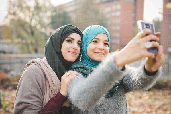 Two female friends in park posing for smartphone selfie Royalty-free stock photo