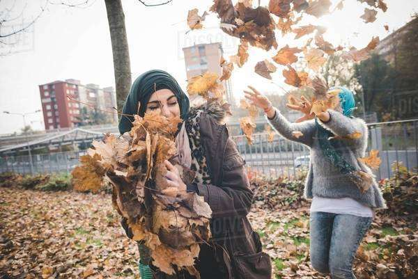 Two young women friends play fighting with autumn leaves in park Royalty-free stock photo