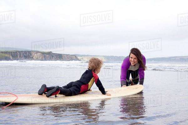 Mother teaching son how to surf Royalty-free stock photo