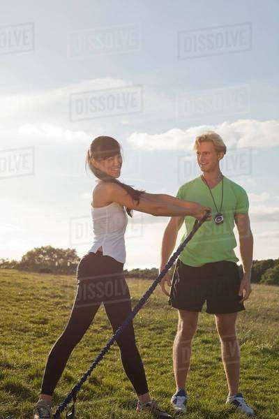 Personal trainer and female client doing stretch exercise Royalty-free stock photo