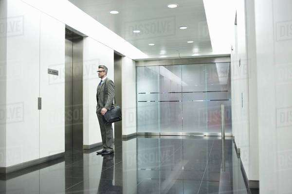 Businessman waiting for elevator in office corridor Royalty-free stock photo