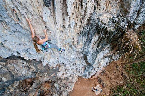 Young female climber climbing a 7a route at Crazy Horse Buttress close to Chiang Mai, Thailand Royalty-free stock photo
