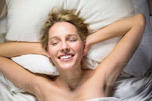 Young woman lying on bed with hands behind head Royalty-free stock photo