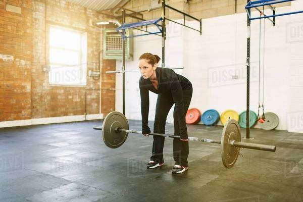 Woman lifting barbell in gym Royalty-free stock photo