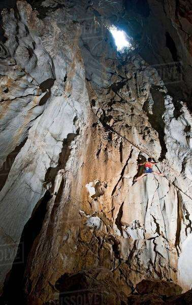 Female climber climbing inside of Anxiety State Crisis Cave, Mae On, Chiang Mai, Thailand Royalty-free stock photo