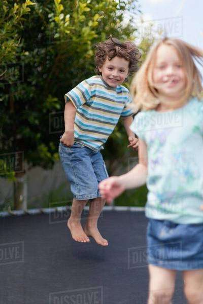 Smiling children jumping on trampoline Royalty-free stock photo