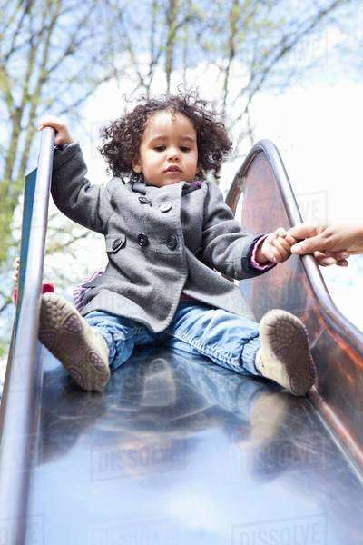 Girl playing on slide in playground Royalty-free stock photo