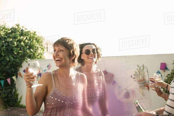 Young women drinking and laughing at poolside party Royalty-free stock photo
