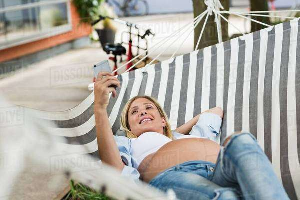 Full term pregnancy young woman lying in hammock taking smartphone selfie Royalty-free stock photo