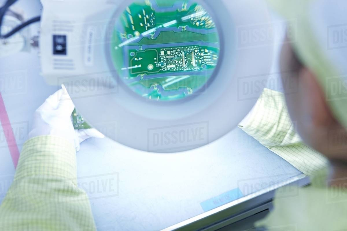 Young Woman Using Magnifier At Quality Check Station Factory Electronic Circuit Book Producing Flexible Boards Plant Is Located In The South Of China