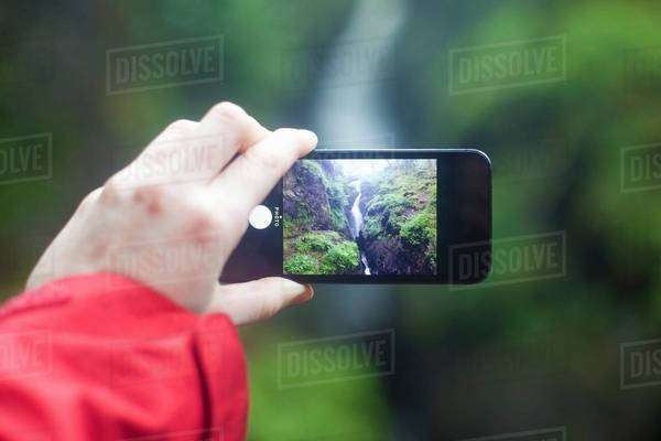 Womans hand holding smartphone, photographing Aira Force waterfall, Penrith, Cumbria, UK Royalty-free stock photo