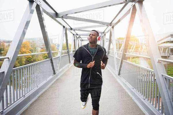 Young man running outdoors, wearing headphones Royalty-free stock photo