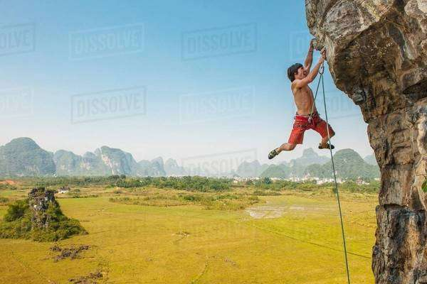 Male climber hanging from the Egg - a lime stone cliff in Yangshuo, Guangxi Zhuang, China Royalty-free stock photo