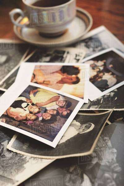 Pile of family photographs on table, next to tea cup Royalty-free stock photo
