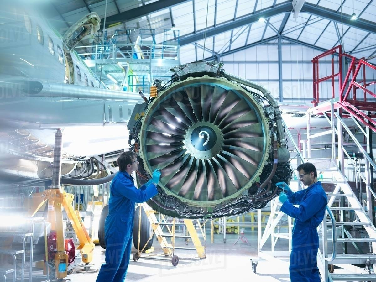 Aircraft engineers working on jet engine in aircraft maintenance factory -  Stock Photo - Dissolve