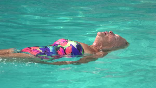 Older Caucasian women swimming with foam noodles in swimming pool Royalty-free stock video