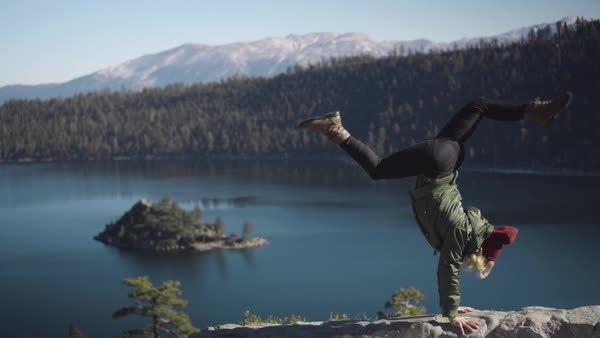 An athletic, young woman in winter apparel, does a handstand on the edge of a mountain with a beautiful lake and island in the background Royalty-free stock video