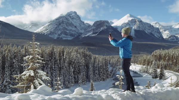 Wide-angle shot of a man photographing mountains with his smartphone Royalty-free stock video