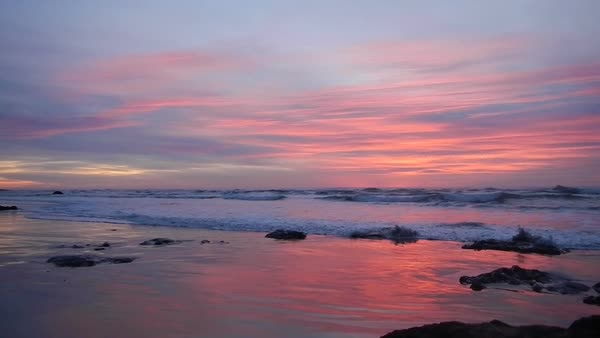 Vivid colors in clouds with waves during sunset over the beautiful Pacific Ocean. Royalty-free stock video