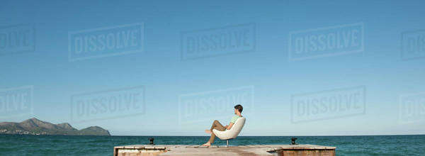 Man siting at end of dock looking at view, rear view Royalty-free stock photo