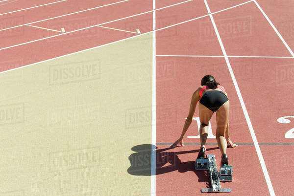 Woman crouched in starting position on running track, rear view Royalty-free stock photo
