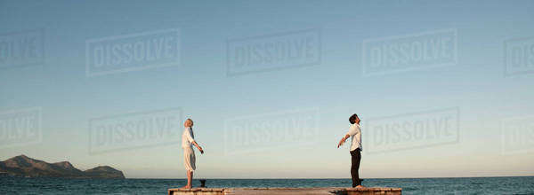 Couple standing back to back on pier, arms out stretched and eyes closed Royalty-free stock photo