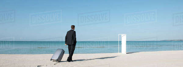 Businessman pulling suitcase on beach, walking towards half-open door Royalty-free stock photo