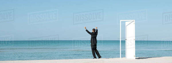 Businessman standing on beach looking at ocean with arms raised, rear view Royalty-free stock photo