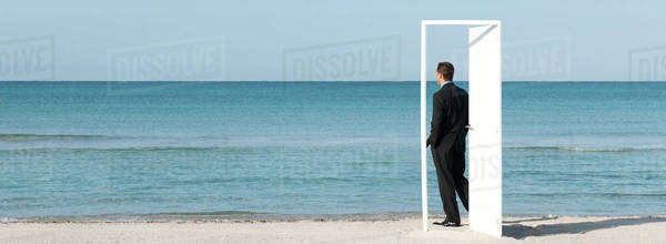 Businessman standing on beach looking at ocean, seen through open door Royalty-free stock photo