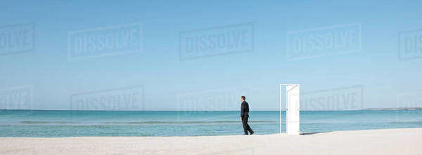Businessman standing on beach next to half-open door, looking at ocean Royalty-free stock photo