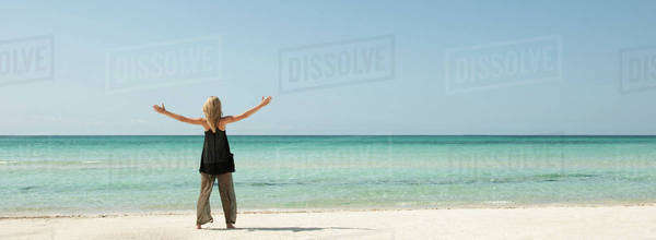 Woman standing on beach with arms outstretched, rear view Royalty-free stock photo