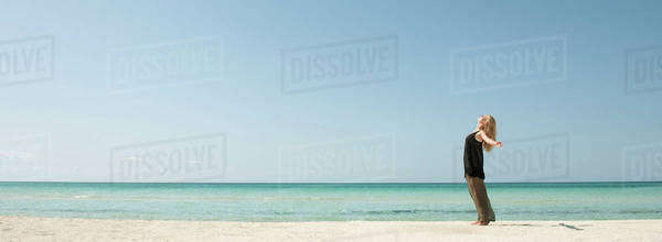 Woman standing on beach with head back and arms outstretched Royalty-free stock photo
