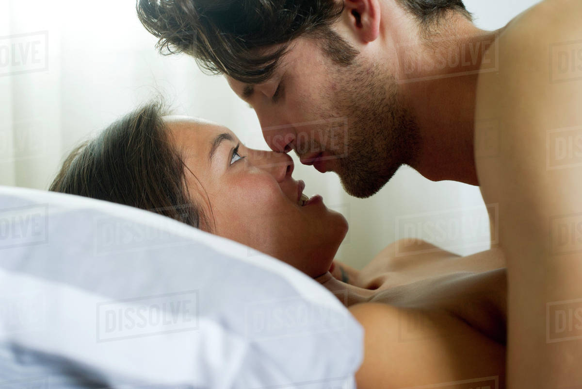 young couple romancing in bed side view stock photo dissolve