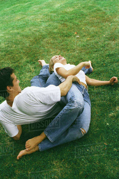 Couple reclining on ground together, laughing, high angle view Royalty-free stock photo