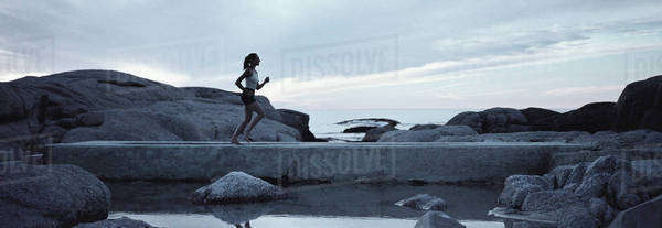 Woman running across footbridge near seashore in early morning Royalty-free stock photo