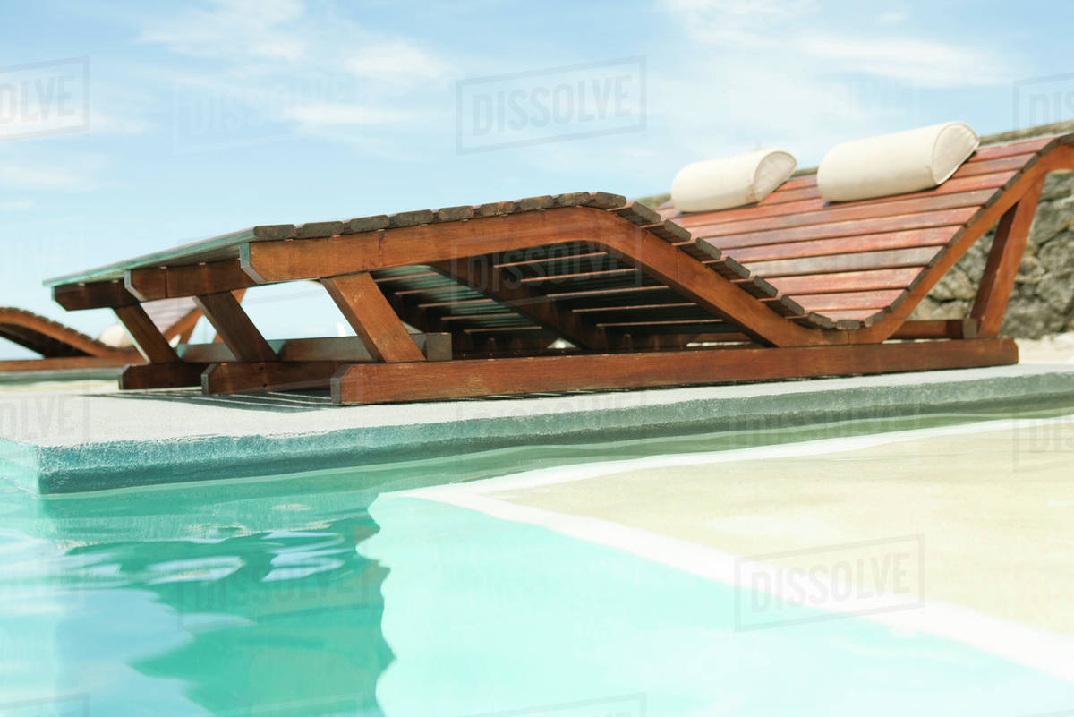 Wooden Lounge Chairs Overlooking Swimming Pool
