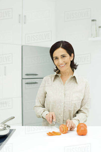 Woman slicing tomatoes in kitchen Royalty-free stock photo