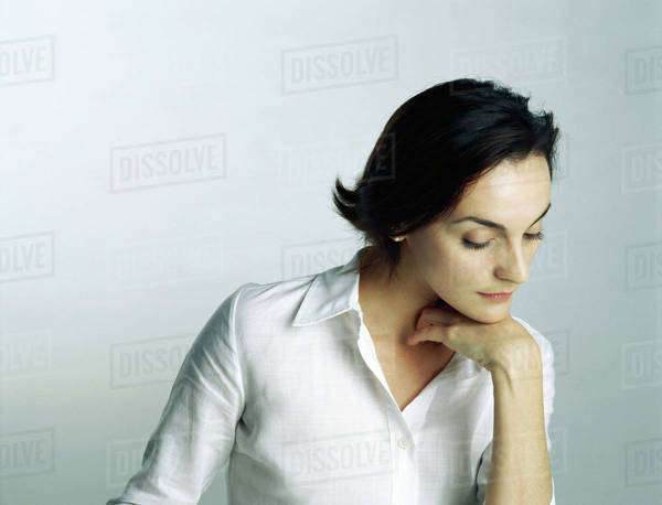 Woman resting chin on hand, looking down, portrait Royalty-free stock photo