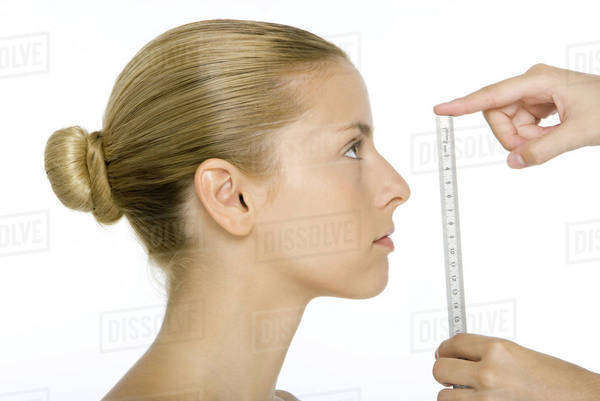 Woman in profile, face being measured by ruler Royalty-free stock photo
