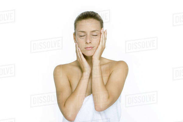 Woman with plastic surgery markings under eyes, holding face, eyes closed Royalty-free stock photo