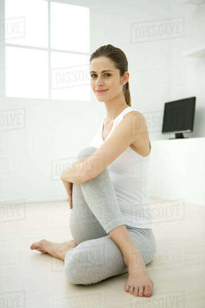 Woman doing spinal twist, smiling at camera Royalty-free stock photo