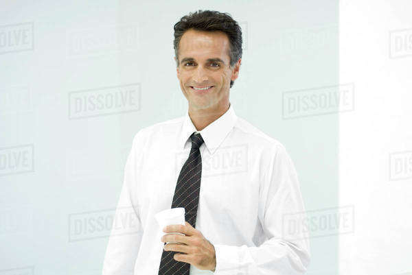 Businessman holding cup, smiling, portrait Royalty-free stock photo