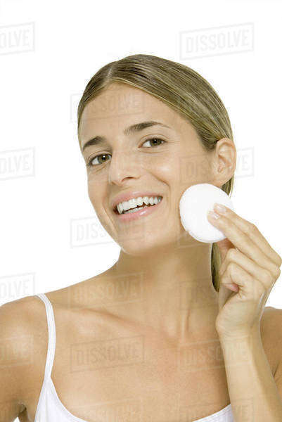 Woman wiping face with cotton cosmetic pad, smiling at camera Royalty-free stock photo