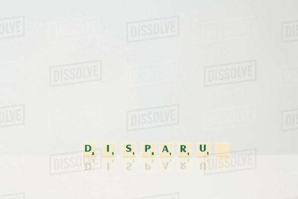 "Word game tiles spelling the word ""Disparu,"" (""disappeared"" in french), with final tile blank Royalty-free stock photo"