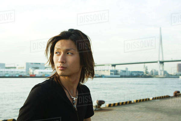 Young Japanese man standing by Tempozan Harbour, Osaka, Japan Royalty-free stock photo