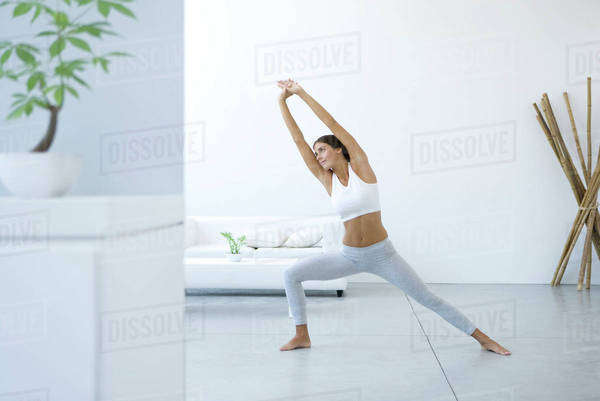Woman performing yoga pose in living room Royalty-free stock photo