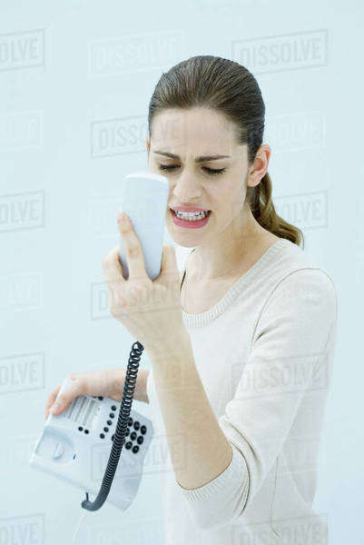 Young woman shouting at landline phone, receiver in hand Royalty-free stock photo