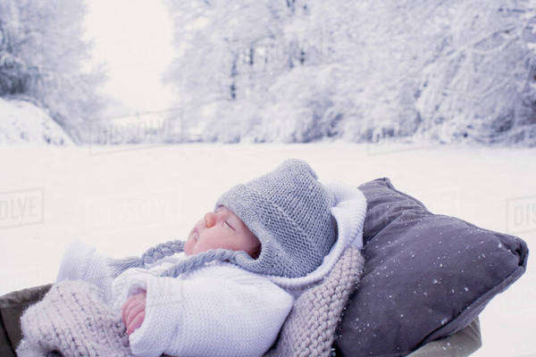 Baby sleeping in bassinet in wintery scane Royalty-free stock photo
