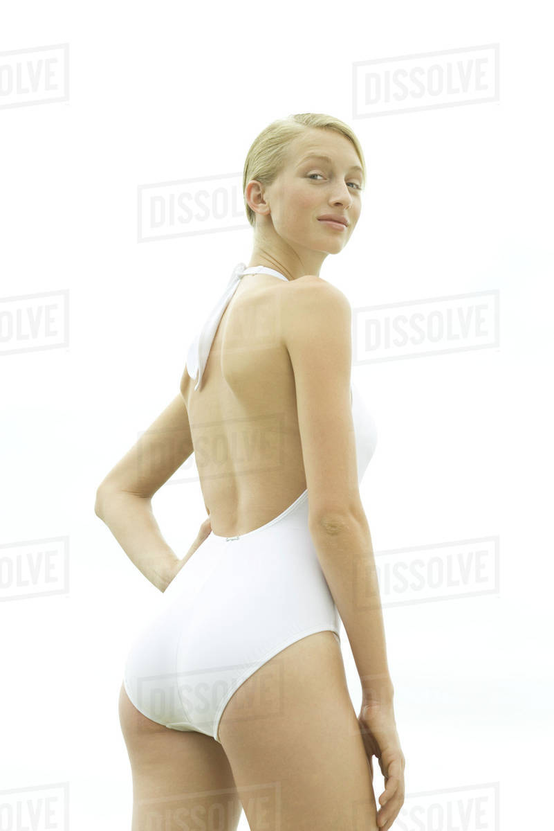 519b754d9c4f2 Teenage girl wearing bathing suit, standing with hand on hip, rear view,  looking over shoulder at camera